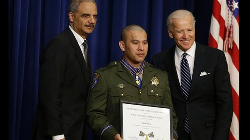 Vice President Joe Biden and Attorney General Eric Holder present the Medal of Valor to Officer Rafael Rivera of the California Highway Patrol, Wednesday, Feb. 20, 2013.