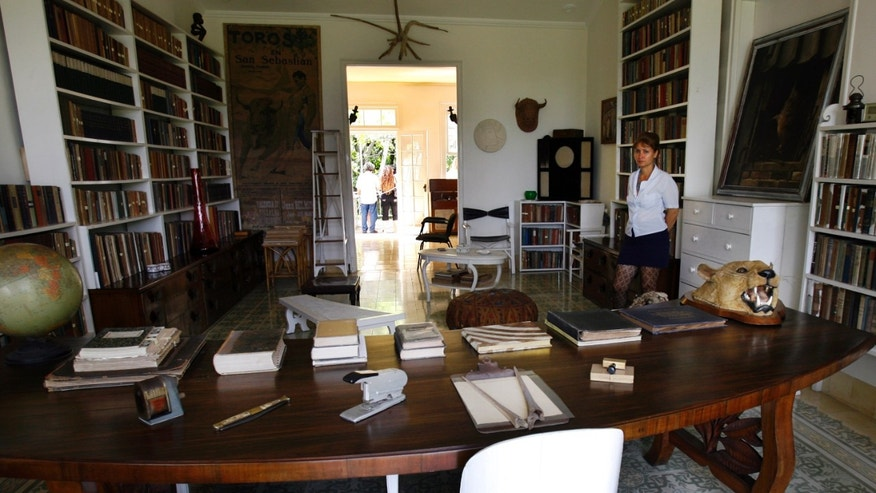 A museum worker in the library of Ernest Hemingway (1899-1961) at his home in Cuba, Finca Vigia.
