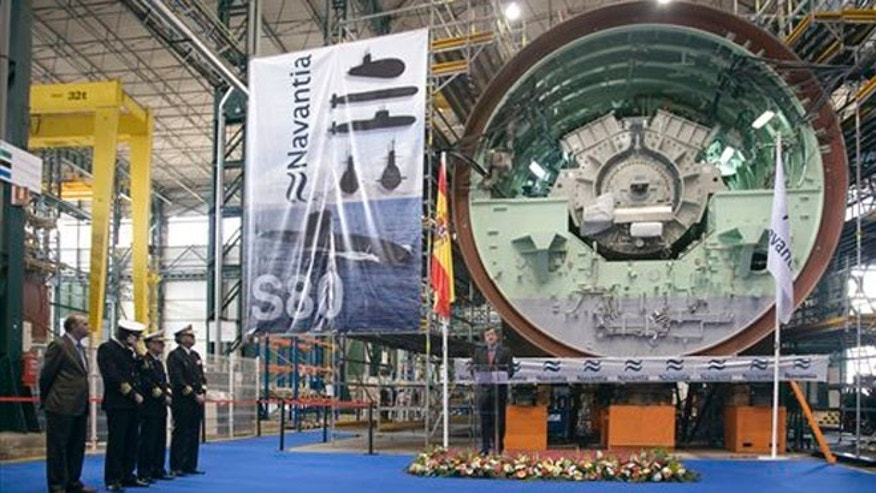 In this Nov. 8, 2012 photo provided by Navantia, Manuel Filgueiras, center, former Cartagena shipyards director, speaks next to the motor of one of the S-80 class submarines in Cartagena, Spain.