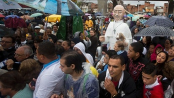 Large puppets that resemble Pope Francis, center, and the Virgin of Aparecida, Brazil's patron saint, partially covered at left, stand tall among residents waiting for Pope Francis' arrival to the Varginha slum Rio de Janeiro, Brazil, Thursday, July 25, 2013. Pope Francis will bless the Olympic flag, visit this slum and address young Roman Catholics in Rio de Janeiro's Copacabana beach on Thursday, as Latin America's first pope continues his inaugural international trip as pontiff. (AP Photo/Victor R. Caivano)