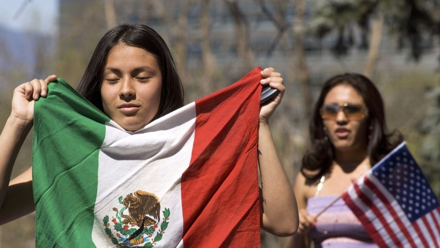 DENVER - APRIL 19:  Daisy Gonzales, 14, (L) displays a Mexican flag during a rally of about 3,000 middle and high school students who walked out of school April 19, 2006 in Denver, Colorado. The students gathered on the steps of the Colorado state Capitol to demonstrate in support of immigrant rights and against U.S. Congressional immigration reform proposals.  (Photo by Kevin Moloney/Getty Images)
