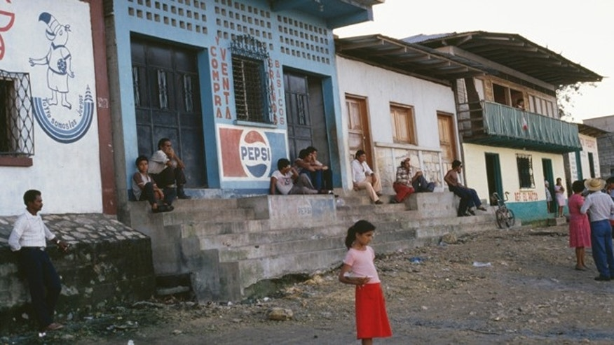 A young girl stands on the side of the road towards the El Ceibal Ruins, Guatemala City, November 1988 (Photo by Frances M. Ginter/Getty Images)