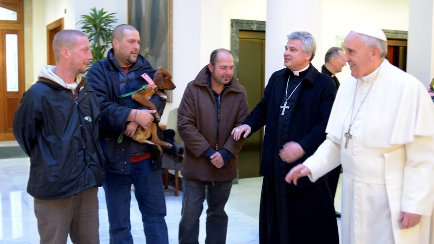 "In this picture provided by the Vatican newspaper L'Osservatore Romano, Pope Francis, right, is flanked by Vatican Almoner Archbishop Konrad Krajewski as he welcomes four men at the Vatican, Tuesday, Dec. 17, 2013. Four homeless people, one of them bringing his dog, helped Pope Francis celebrate his 77th birthday at the Vatican Tuesday. They live on the street in the Rome neighborhood just outside the Holy See's walls and were invited by the Vatican official in charge of alms-giving to attend the morning Mass which Francis celebrates daily at the hotel where he lives on Vatican City grounds, the Vatican said. One of the men held his dog as he was presented to Francis after the guests chatted following Mass. The Vatican also said Francis invited his household help to join him in a ""family-like"" atmosphere, and he spoke of them one by one during his homily. (AP Photo/L'Osservatore Romano)"
