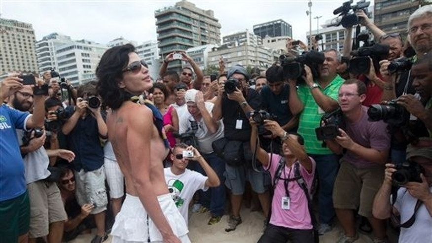 "A woman poses for photos during a protest against a topless ban on the Ipanema beach, in Rio de Janeiro, Brazil, Saturday, Dec. 21, 2013. A much-hyped protest for the right to go topless on Rio de Janeiro's beaches fell flat Saturday when only a handful of women bared their chests for the movement. Under Brazil's penal code, which dates back to the 1940s, female toplessness is an ""obscene act,"" punishable by three months to a year in prison, or fines. (AP Photo/Silvia Izquierdo)"