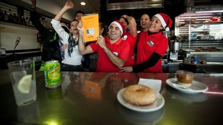 "Gas station workers celebrate after winning the second prize of the Christmas lottery El Gordo (The Fat One) in Santa Cruz de Tenerife in the Canary Islands, Spain, Sunday Dec. 22, 2013. Millions of Spaniards are glued to televisions as the country's cherished Christmas lottery, the world's richest, distributes a bounty of 2.5 billion euros ($3.4 billion) in prize money to winning ticket owners. The draw is so popular that most of Spain's 46 million inhabitants traditionally watch some part of it live in the hope that the school children singing out winning numbers will call out their ticket. The top prize, known as ""El Gordo"" (The Fat One), gives lucky winners 400,000 euros per ticket Sunday, while the second-best number nets 125,000 euros. (AP Photo/Andres Gutierrez)"
