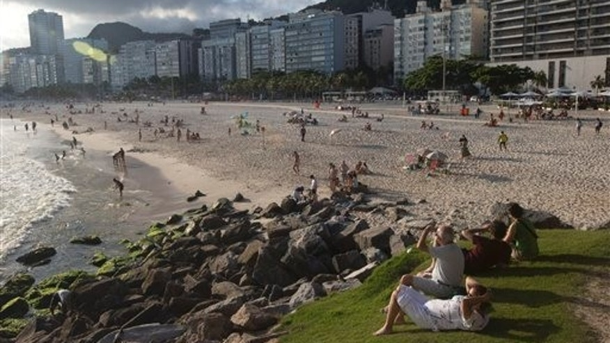 Tourists sit on a patch of grass along the Copacabana beach shore in Rio de Janeiro, Brazil, Thursday, Dec. 26, 2013. Tourists visiting the city for the 2014 World Cup could end up paying three times more for hotels compared to those coming for the Olympics two years later, according to recent industry studies and research by The Associated Press. (AP Photo/Silvia Izquierdo)