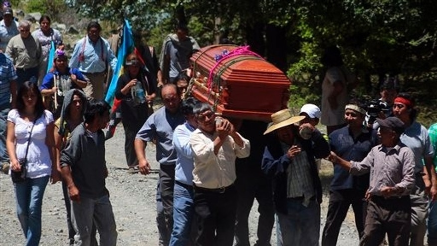 People carry the casket of Nicolasa Quintreman, a Mapuche Indian leader, during her funeral in Ralco, Chile, Friday, Dec. 27, 2013. The 73-year-old Mapuche Indian leader was found floating Tuesday in a reservoir she spent a decade trying to prevent from being created. Quintreman became a national figure during protests against the construction of a hydroelectric dam on tribal land in the forested mountains of southern Chile. (AP Photo/Victor Salazar, AgenciaUno)