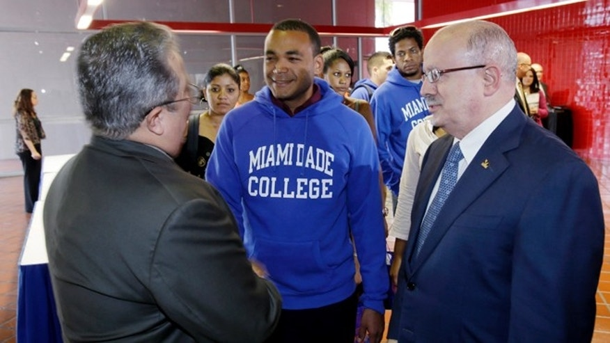 Victór Vazquez Hernández, left, Assistant Professor of the Social Science Department and Eduardo Padrón, right, president of Miami Dade College, greet students from Cuba as they arrive at a news conference, Monday, Jan. 13, 2014 for the announcement of their arrival at Miami Dade College in Miami. The group of students from Cuba is opening the communist country's first academic trip in more than five decades to the largest public college in Miami.   (AP Photo/Wilfredo Lee)