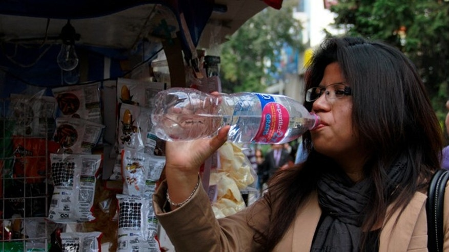 In this Jan. 9, 2014 photo, a woman drinks bottled water in Mexico City. Bad tap water accounts in part for Mexico being the highest consumer of bottled water and sweetened drinks. A law recently approved by Mexico Cityâs legislators will require all restaurants to install filters, offering patrons free, apparently drinkable potable water that wonât lead to stomach problems and other ailments. With an obesity epidemic looming nationwide, the cityâs health department decided to back the water initiative. (AP Photo/Marco Ugarte)