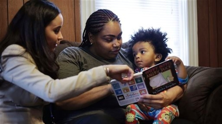 In this Feb. 3, 2014 photo, caseworker and home visitor Stephanie Taveras, left, reads a book with Ashley Cox, center, and Cox's 16-month-old son Jaiden, right, at the family's home in Providence, R.I. The city has begun an effort to boost language skills for children from low-income families by equipping them with audio recorders that count every word they hear. During home visits, social workers go over the word counts with parents and suggest tips to boost the childs language skills. (AP Photo/Steven Senne)
