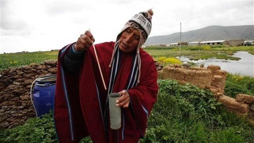 Meteorologist Francisco Condori measures rain water with a flow meter in Cutusuma, on Lake Titicaca's Bolivia.