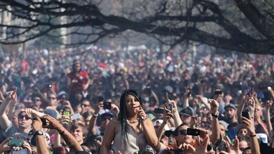 Partygoers listen to live music on the second of two days at the annual 4/20 marijuana festival in Denver, Sunday April 20, 2014. The annual event is the first 420 marijuana celebration since retail marijuana stores began selling in January 2014. (AP Photo/Brennan Linsley)