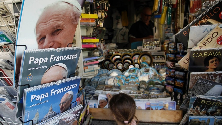 A child picks up a souvenir at a newspaper kiosk near the Vatican, Friday, April 25, 2014. Hundred thousands of pilgrims and faithful are expected to reach Rome to attend the scheduled April 27 ceremony at the Vatican in which Pope Francis will elevate in a solemn ceremony John XXIII and John Paul II to sainthood. (AP Photo/Gregorio Borgia)