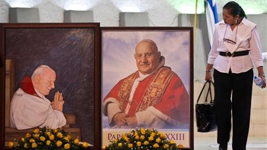 "A woman walks next to portraits of late Pope John Paul II, left, and Pope John XXIII before a vigil at a Metropolitan cathedral in Managua, Nicaragua, Saturday, April 26, 2014. The banner reads in Spanish ""We celebrate the lives of two men who fought to make this a better world."" About 1 million pilgrims are expected to be witnesses in Rome as retired pontiff Benedict XVI will help Pope Francis celebrate the sainthood ceremony Sunday for John Paul II and John XXIII, setting the stage for an unprecedented occurrence of two living popes canonizing two of their predecessors. (AP Photo/Esteban Felix)"