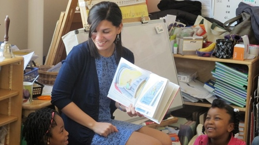 "FILE - In this April 10, 2014 file photo, student teacher Franchesca Moreno, 21, reads to  Andreanna Thomas, 6, right, and Alana Cawthon, upper left, at Bennett Park Montessori School in Buffalo, N.Y. Moreno is among the first future New York teachers required to pass a kind of ""bar exam"" to become professionally certified. (AP Photo)"