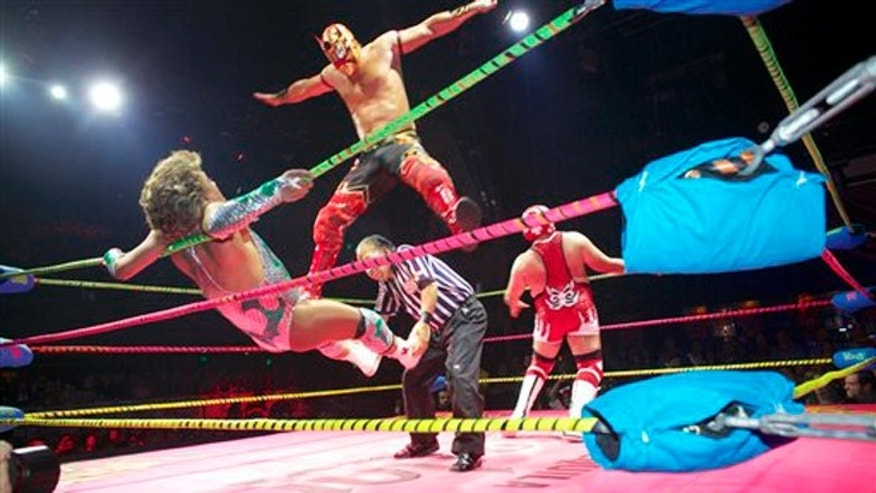 In this Wednesday, Feb. 12, 2014 photo, wrestler Niebla Roja, top, flies over referee Platainitos, to land on wrestler Cassandro, left, during a performance at Lucha VaVoom's Valentineâs show at The Mayan Theatre downtown Los Angeles. At right, wrestler, Dr. Maldad.  The esoteric hybrid of American burlesque and Mexican wrestling is an outrageous hit. (AP Photo/Damian Dovarganes)