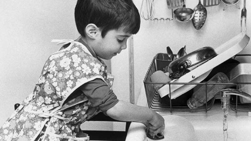 Young Jean helps out with the washing up, circa 1955. (Photo by Susan Schiff Faludi/Three Lions/Hulton Archive/Getty Images)