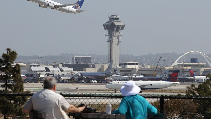 LOS ANGELES, CA - APRIL 22:  People watch as a United Airlines jet passes the air traffic control tower at Los Angles International Airport (LAX) during take-off on April 22, 2013 in Los Angeles, California. Delays have been reported throughout the nation because of the furloughing of air traffic controllers under sequestration. The average delay overnight in the Southern California Terminal Radius Approach Control (TRACON) was was three hours.  (Photo by David McNew/Getty Images)