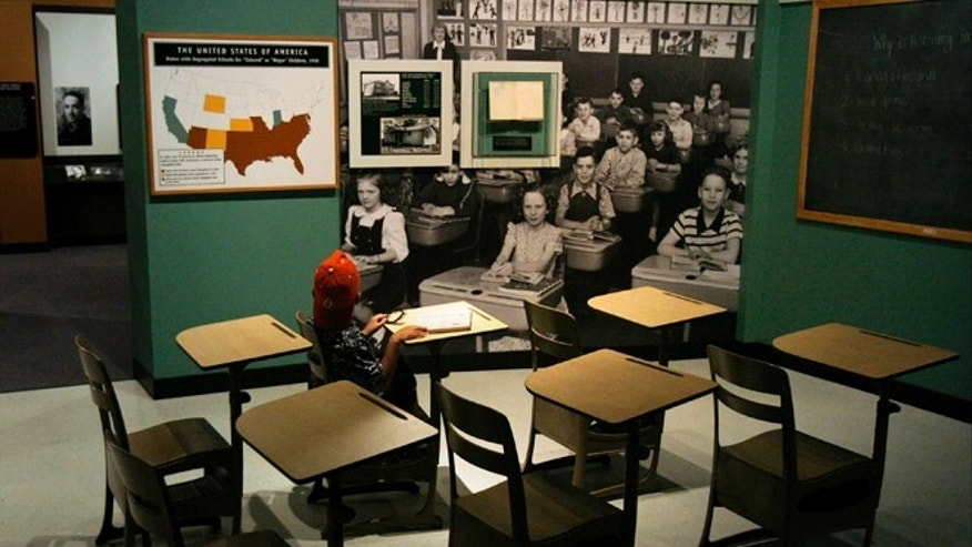 "WASHINGTON - MAY 15:  Jordan Maclin, 6 of Maryland, sits in a Brown vs Board of Ed era classroom at the ""Separate But Not Equal"" exhibit at the Smithsonian's American History Museum, May 15, 2004 in Washington, DC.  May marks the 50th anniversary of the historic Civil Right Era US Supreme Court Decision.  (Photo by Brendan Smialowski/Getty Images)"