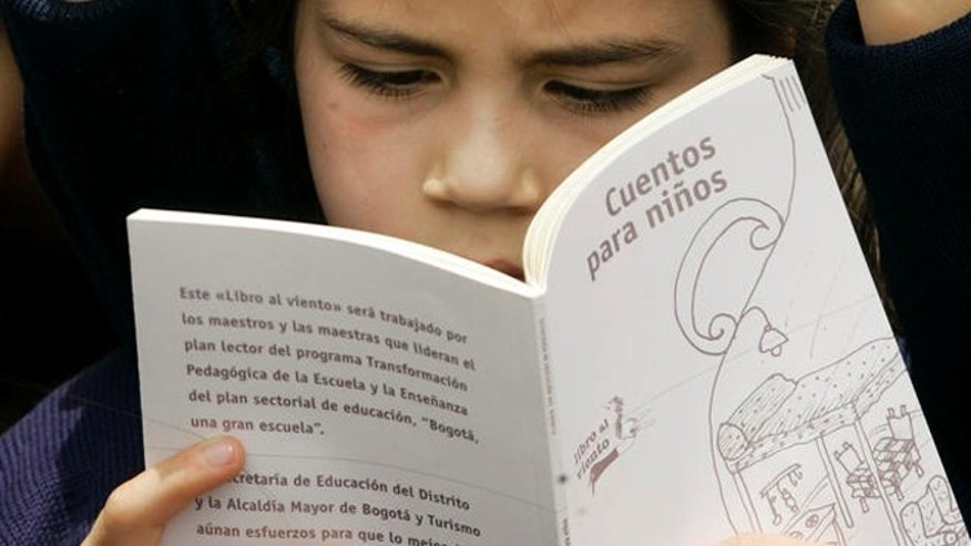 A girl reads a book during a ceremony to celebrate that UNESCO has designated Bogota as the 2007 World Book Capital, at the Bolivar's square, in Bogota, Monday, April 23, 2007. (AP Photo/Fernando Vergara)