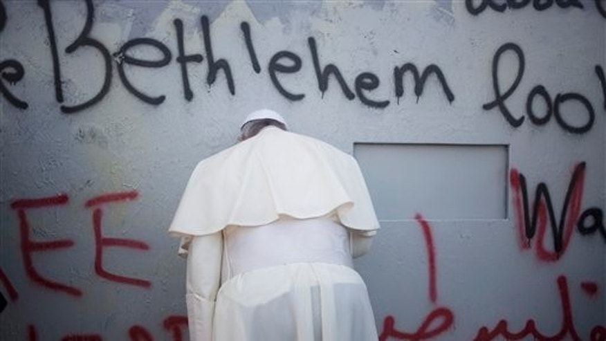 "Pope Francis prays at Israel's separation barrier on his way to a mass in Manger Square next to the Church of the Nativity, traditionally believed to be the birthplace of Jesus Christ in the West Bank city of Bethlehem on Sunday, May 25, 2014. Francis called the Israeli-Palestinian stalemate ""unacceptable"" as he landed Sunday in the West Bank town of Bethlehem in a symbolic nod to Palestinian aspirations for their own state. (AP Photo/Ariel Schalit)"