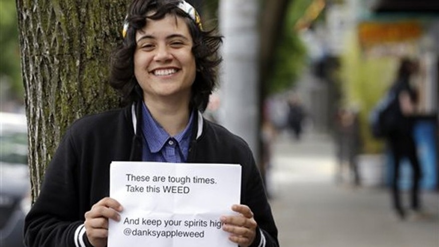 "Yeni Sleidi, known as the ""weed fairy,"" poses for a photo in Seattleâs Capitol Hill neighborhood Wednesday, May 28, 2014, where this past weekend she posted 50 fliers with nuggets of marijuana taped to them. Sleidi, a 23-year-old who works in social media, has been visiting Seattle from New York where last year she did a similar posting, albeit anonymously. (AP Photo/Elaine Thompson)"