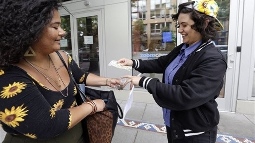 "Yeni Sleidi, known as the ""weed fairy,"" right, buys marijuana from a dealer, who declined to be identified, in Seattles Capitol Hill neighborhood Wednesday, May 28, 2014, where this past weekend Sleidi posted 50 fliers with nuggets of marijuana taped to them. Sleidi, a 23-year-old who works in social media, has been visiting Seattle from New York where last year she did a similar posting, albeit anonymously. (AP Photo/Elaine Thompson)"