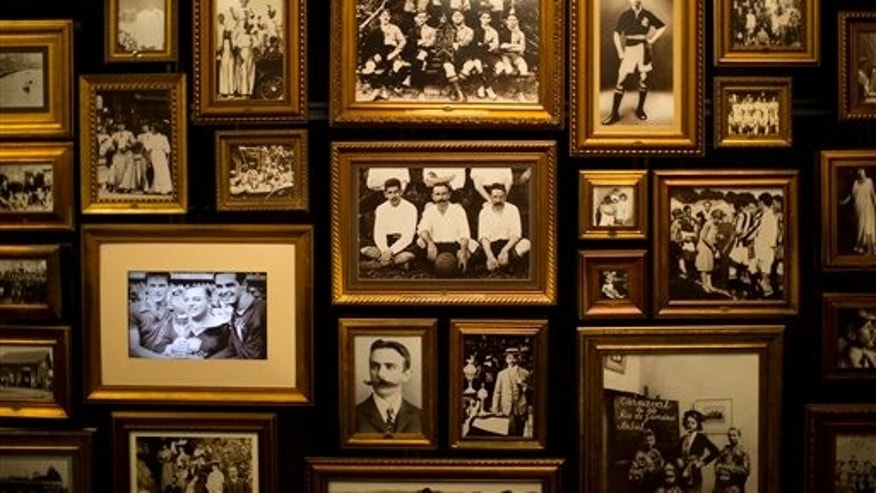 In this June 12, 2014 photo, a photo of Charles Miller seated with two other players, center with a large mustache, hangs with other pictures of him in the Hall of Origins at the Soccer Museum in Sao Paulo, Brazil. Miller knew the largest megacity in the southern hemisphere when it was a more unassuming place and many residents were immigrants from Italy. He's hailed as the forefather of Brazilian football because he is widely credited as having organized the first proper game of football according to rules first drawn up in a London. (AP Photo/Dario Lopez-Mills)