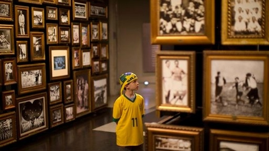 In this June 12, 2014 photo, a young Brazil soccer fan visits the Hall of Origins at the Soccer Museum in Sao Paulo, Brazil. It's now 120 years since Charles Miller stepped off a boat from England carrying two footballs, an air pump to fill them, his football boots and a set of rules for the game. (AP Photo/Dario Lopez-Mills)
