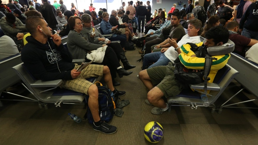 Passengers wait after flights were delayed due to heavy fog, in World Cup host city Curitiba, Brazil, June 17, 2014.