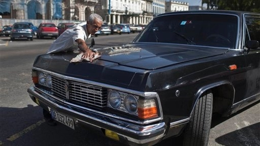 In this June 18, 2014 photo, taxi driver Moises Suarez cleans the Soviet-made limousine he drives which was once part of Fidel Castro's fleet in Havana, Cuba. The fleet was often used to ferry around visiting dignitaries, and at least one of the limos was used occasionally by Castro himself, though he usually preferred a military-style jeep for his own transportation needs. (AP Photo/Franklin Reyes)