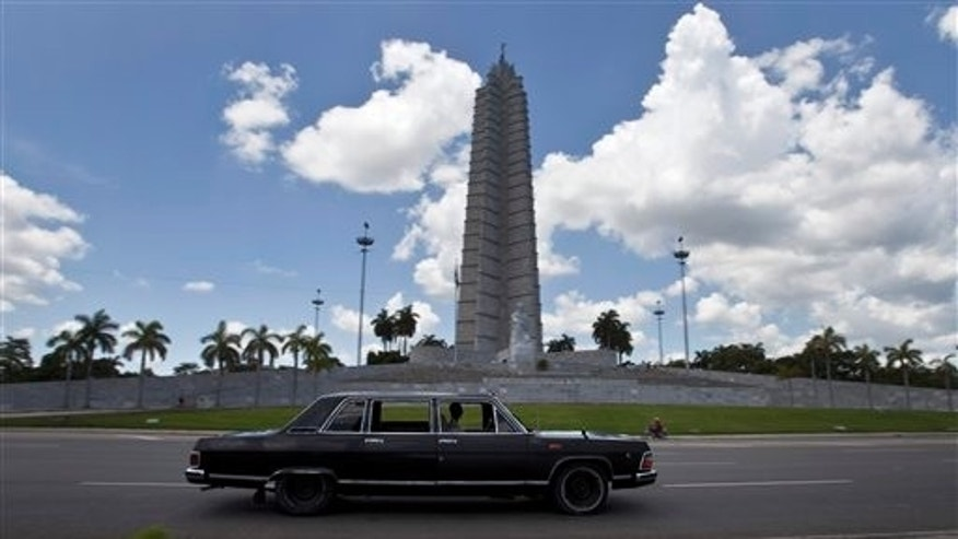 "In this June 18, 2014 photo, taxi driver Moises Suarez drives past Revolution Plaza the Soviet-made limousine that once was part of Fidel Castro's fleet, which he rents from the government, in Havana, Cuba. ""A lot of drivers pull up next to me at stoplights,"" Suarez said. ""They start laughing and they say, 'You never imagined you would be driving the comandante's car, eh?'""(AP Photo/Franklin Reyes)"