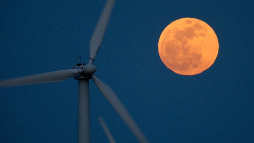 PALM SPRINGS, CA - MAY 5:  A perigee moon, or supermoon, rises behind wind turbines on May 5, 2012 near Palm Springs, California. The moon appears especially big and bright during this once-a-year cosmic event as the full moon is at its closest to the Earth in its elliptical orbit. The perigee side of its orbit is about 31,000 miles closer than the opposite, or apogee, side. The bright light of the full moon also hides all but the brightest meteors of the Eta Aquarid meteor shower, the remnant debris trail of Halley's Comet.   (Photo by David McNew/Getty Images)
