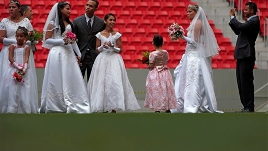 A groom makes pictures as couples gather for a collective civil marriage ceremony on the pitch at the Estadio Nacional, in Brasilia, Brazil, Saturday, July 26, 2014. One hundred couples tied the knot in the mass wedding held in the first post-World Cup event held in the Brazilian capital's Estadio Nacional. The stadium hosted seven games of the recently concluded World Cup, including the one in which the Netherlands won third place after defeating Brazil 3-0. (AP Photo/Eraldo Peres)