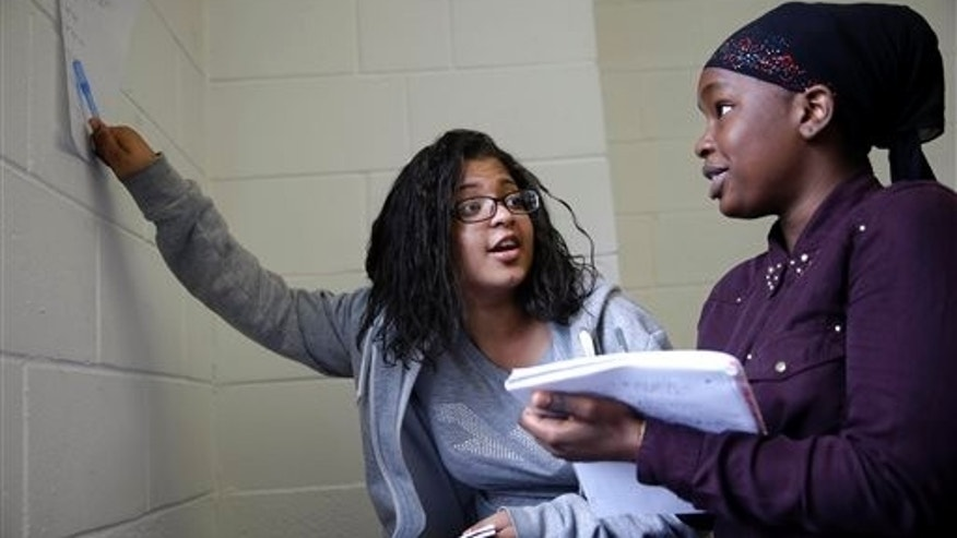 In this July 16, 2014 photo, Paola Francisco, 16, left and Salma Bah, 16, work together on a math problem in an Upward Bound program that serves as a pathway to college for students from low-income families, in New York. National Upward Bound alumni include Oprah Winfrey, actresses Viola Davis and Angela Bassett, ABC News correspondent John Quinones, and Democratic political strategist Donna Brazile. (AP Photo/Seth Wenig)