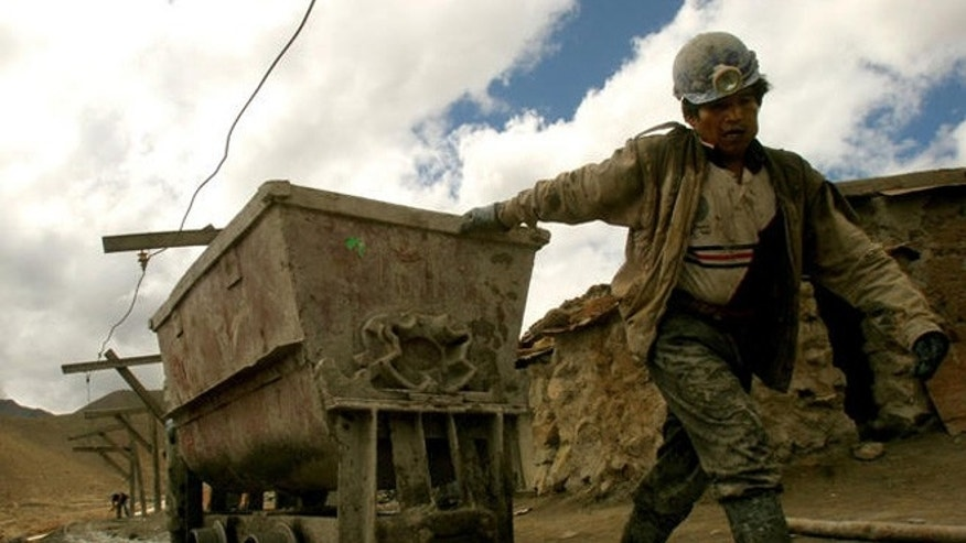 An independent miner leaves the Candelaria zinc-tin mine pulling a two-tons wagon loaded with poorly concentrated mineral at the famous Cerro Rico mountain in Potosi, Bolivia, Feb. 12, 2007. (AP Photo/Dado Galdieri)