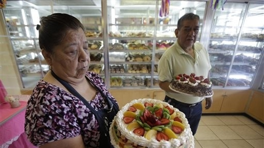 In this July 31, 2014, photo, Concepcion Flores, owner of Panaderia Flores, holds a gelatina cake on Salt Lake City's west side. Panaderia Flores offers sweet breads, pineapple or pumpkin empanadas and tamales. (AP Photo/Rick Bowmer)