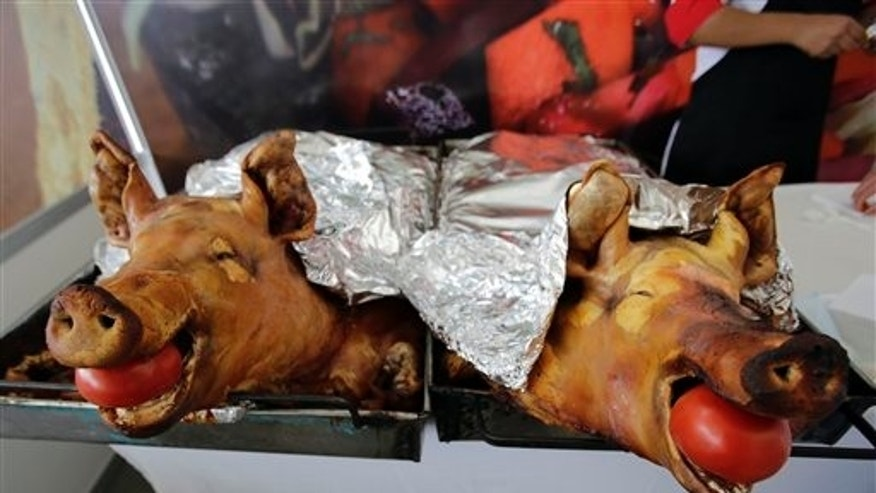 "In this Aug. 17, 2014 photo, slow-roasted pork known as ""Hornado,"" a traditional dish consisting of marinated, slow-roasted pork, is presented before the judges of the national contest to choose the country's best ""Hornado,"" in Riobamba, Ecuador. After years of disputes within the different regions of Ecuador, over who could make the best ""Hornado,"" the championship on Sunday finally settled the issue. (AP Photo/Dolores Ochoa)"