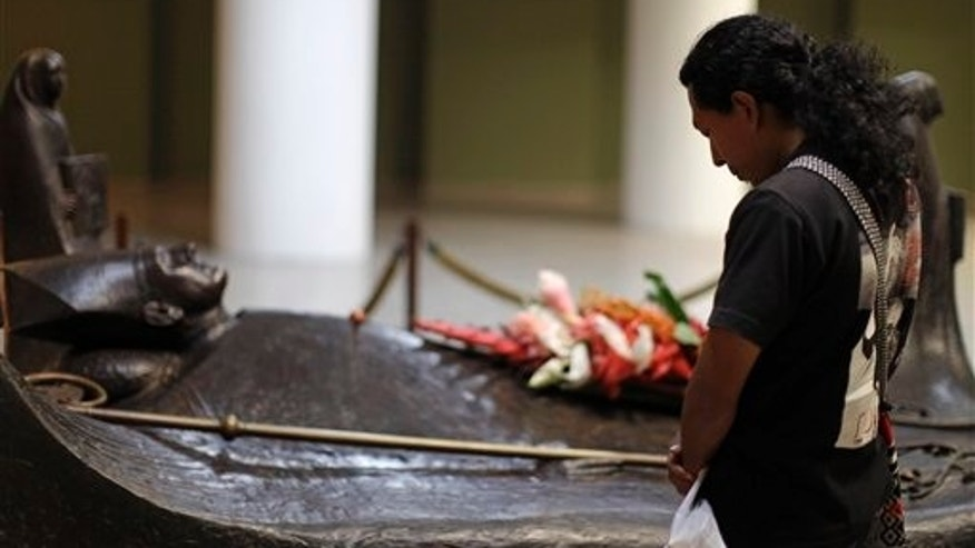 FILE - In this March 23, 2011, file photo, a man prays next to the tomb of slain Roman Catholic Archbishop Oscar Arnulfo Romero inside the national cathedral in San Salvador, El Salvador.