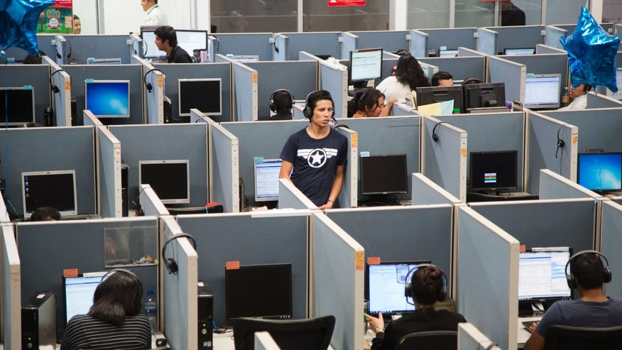 In this Aug. 13, 2014 photo, a man stands in the middle of the Firstkontact Center, a call center in the northern border city of Tijuana, Mexico. Many Mexicans deported under U.S. President Barack Obama are finding employment in call centers in Tijuana and other border cities. In perfect English, some dont even speak Spanish, they talk to American consumers who buy gadgets and gizmos, have questions about warrantees and complain about overdue deliveries. The call center industry has prospered in Mexican border cities as deportations spiked under U.S. President Barack Obama. (AP Photo/Alex Cossio)