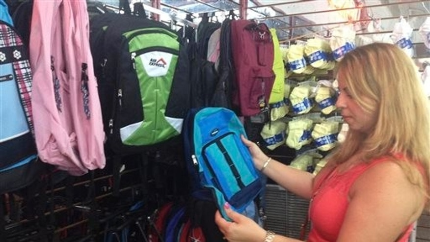 In this, Saturday, Aug. 23, 2014 photo, Anais Montes de Oca, 35, looks at backpacks for sale at the Nooo Que Barato store in Hialeah, Fla. She is one of many Cubans living in the U.S. who buy school supplies for young relatives in Cuba. In response to demand, discount stores like Nooo Que Barato even sell a version of the burgundy-red uniform used by primary students on the island. (AP Photo/Christine Armario)