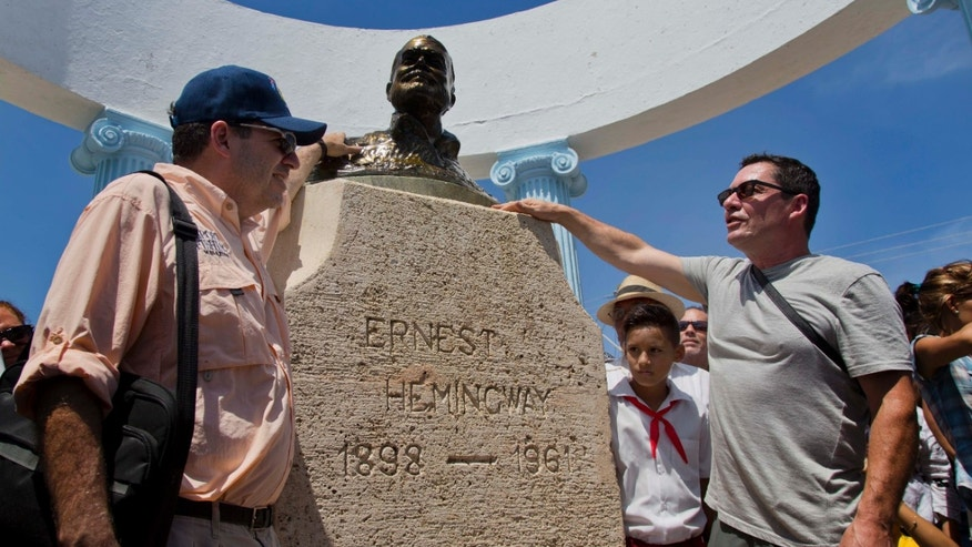 John Hemingway, left, and his brother Patrick pose with a statue of their grandfather Ernest Hemingway in Cojimar, Cuba, Monday, Sept. 8, 2014. Along with a team of U.S. researchers, the Hemingway brothers are on a five-day mission to leverage their famous name to encourage closer ties between the United States and Cuba and, hopefully, open the way for scientists to gain access to the writer's fishing logs, a long-concealed and potentially valuable source of knowledge about the area's massive predatory game fish. (AP Photo/Ramon Espinosa)