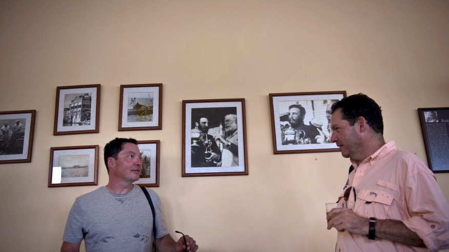 John Hemingway, right, speaks with his brother Patrick next to photos of their grandfather Ernest Hemingway with Fidel Castro as they arrive to eat at La Terraza restaurant in Cojimar, Cuba, Monday, Sept. 8, 2014. Along with a team of U.S. researchers, the Hemingway brothers are on a five-day mission to leverage their famous name to encourage closer ties between the United States and Cuba and, hopefully, open the way for scientists to gain access to the writer's fishing logs, a long-concealed and potentially valuable source of knowledge about the area's massive predatory game fish. (AP Photo/Ramon Espinosa)