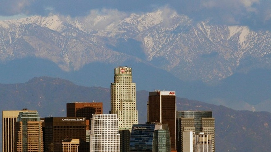 FILE - In this Dec. 27, 2012 file photo, snow covered San Gabriel Mountains rise behind the downtown Los Angeles downtown skyline. President Barack Obama plans to announce on Friday, Oct. 10, 2014 that he will designate 346,000 acres within the San Gabriel Mountains as the nation's new national monument. (AP Photo/Nick Ut, File)