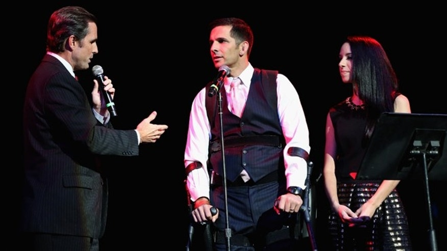 NEW YORK, NY - NOVEMBER 05:  (L-R) Bob Woodruff, Derek Herrera, Captain, US Marine Corps, Active and Maura Herrera walks onstage at 2014 Stand Up For Heroes at Madison Square Garden at Madison Square Garden on November 5, 2014 in New York City.  (Photo by Monica Schipper/Getty Images for New York Comedy Festival)