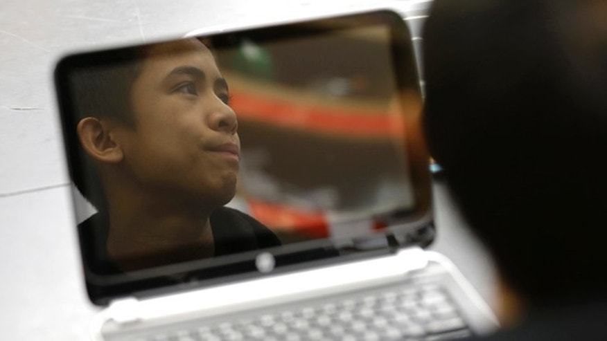 Joven Palma, 13, is reflected in the screen of a laptop computer, Tuesday, Dec. 9, 2014, at Pacific Middle School in Des Moines, Wash., as he listens to instructions for taking part in the international Hour of Code project. The project seeks to increase interest and education in computer science by exposing students to an hour or more of simple computer programing. (AP Photo/Ted S. Warren)