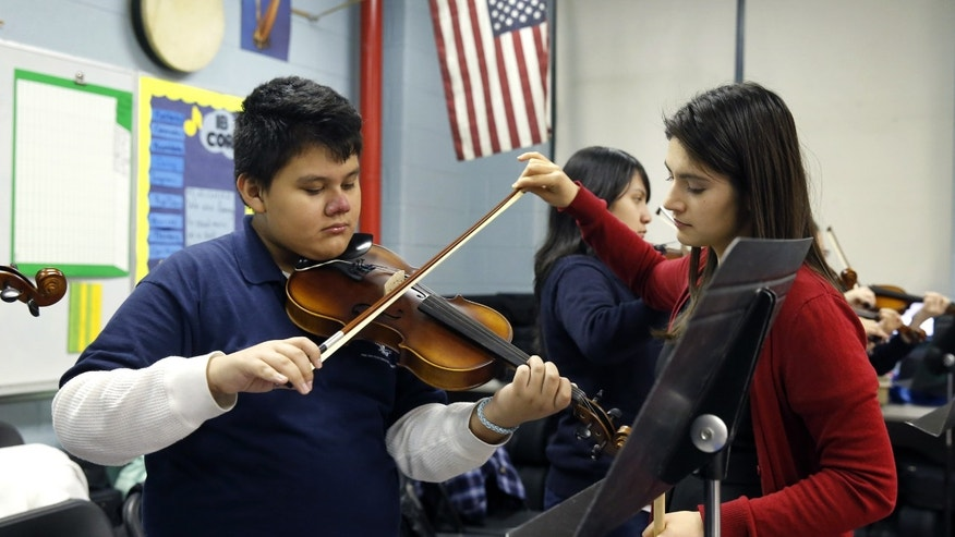FILE - In this Dec. 12, 2014 file photo, music teacher Maria Pulido, right, works with Brian Gonzalez on his violin at the Richard Edwards Elementary School in Chicago, Illinois. Chicago now joins dozens of school districts across the country that teach mariachi music in schools. It's a way to connect schools and parents, many who speak Spanish, from Hispanic communities, say organizers. (AP Photo/Charles Rex Arbogast, File)