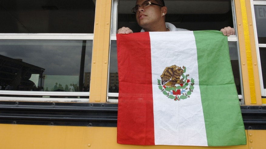 DALLAS - MARCH 27:  An unidentified student displays a Mexican flag as he rides a bus back to school after protesting in front of Dallas City Hall March 27, 2006 in Dallas, Texas. Hispanic high school students from the Dallas area left school to rally on the front steps of City Hall in protest of immigration reform bill HR4437, which considers an unlawful presence in the U.S. a felony, with undocumented immigrants facing potential jail time.  (Photo by Jensen Walker/Getty Images)