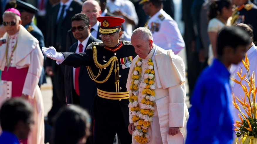 Chief of defence staff Gen. Jagath Jayasuriya leads Pope Francis at the airport in Colombo, Sri Lanka, Tuesday, Jan. 13, 2015. Francis arrived in Sri Lanka on Tuesday at the start of a weeklong Asian tour, saying the island nation can't fully heal from a quarter-century of ethnic civil war without pursuing the truth about the injustices that were committed. (AP Photo/Saurabh Das)