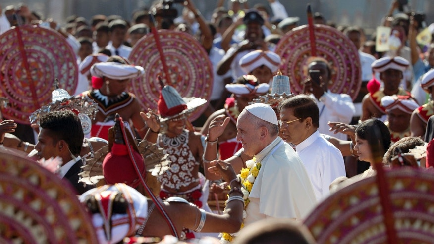 Pope Francis is received by colorful Sri Lankan dancers upon arrival at Colombo's International airport in Colombo, Sri Lanka, Tuesday, Jan. 13, 2015.  Pope Francis arrived in Sri Lanka Tuesday at the start of a weeklong Asian tour saying the island nation can't fully heal from a quarter-century of ethnic civil war without pursuing truth for the injustices committed.  (AP Photo/Alessandra Tarantino)